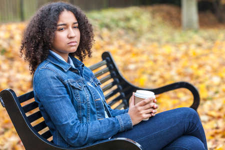 sad: Beautiful mixed race African American girl teenager female young woman drinking takeaway coffee outside sitting on a park bench in autumn or fall looking sad depressed or thoughtful