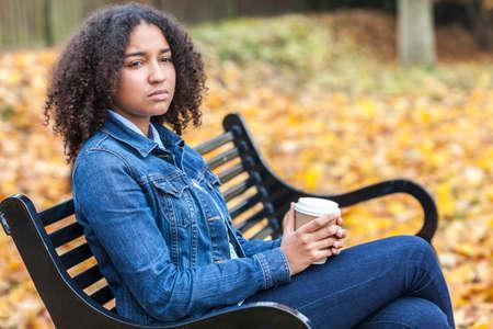 bambini pensierosi: Bella gara mista ragazza afroamericana adolescente femminile giovane donna che beve caffè da asporto fuori seduto su una panchina in autunno o caduta che sembra triste o depresso riflessivo