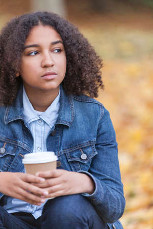 depressed teenager: Beautiful mixed race African American girl teenager female young woman drinking takeaway coffee outside sitting in a park in autumn or fall looking sad depressed or thoughtful
