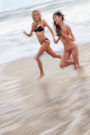 lesbian girls: Motion blurred photograph of young women girls in bikinis running on a beach