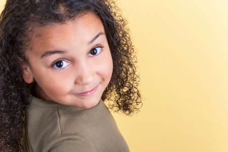 mixed race girl: Studio shot of a beautiful young mixed race girl smiling and looking back over her shoulder