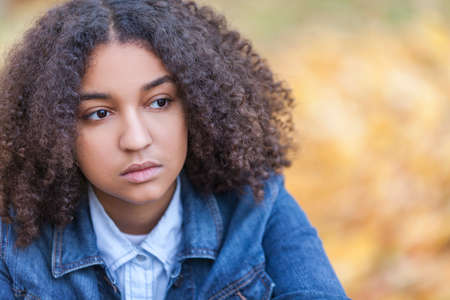 curly hair child: Beautiful mixed race African American girl teenager female young woman outside in autumn or fall looking sad depressed or thoughtful