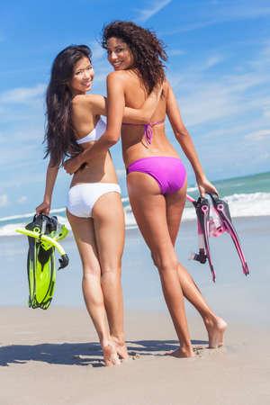 women friendship: Beautiful young women girls in bikinis with diving equipment on a beach
