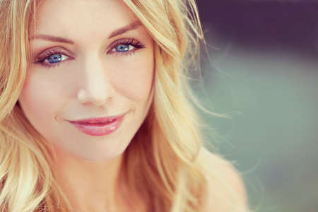 twenties: portrait of naturally beautiful woman in her twenties with blond hair and blue eyes, shot outside in natural sunlight