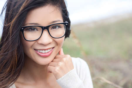 specs: Smiling happy beautiful young Asian Chinese woman or girl wearing geek glasses outside Stock Photo