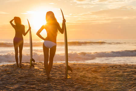 sexy young girls: Вид сзади силуэт двух красивых сексуальных молодых женщин серфер девушки в бикини с доски для серфинга на пляже на закате или восходе солнца