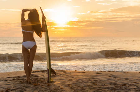 woman sunset: Rear view of beautiful sexy young woman surfer girl in bikini with white surfboard on a beach at sunset or sunrise
