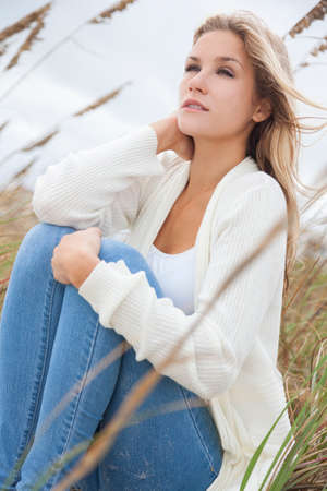 woman resting: A beautiful blond woman or girl wearing jeans siiting in tall grass on a beach