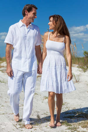 romantic sky: Middle aged man and woman romantic couple in white clothes walking on a deserted tropical beach with bright clear blue sky Stock Photo