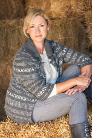 barn boots: Attractive middle aged blond woman sitting on a hay bale in a barn wearing boots Stock Photo