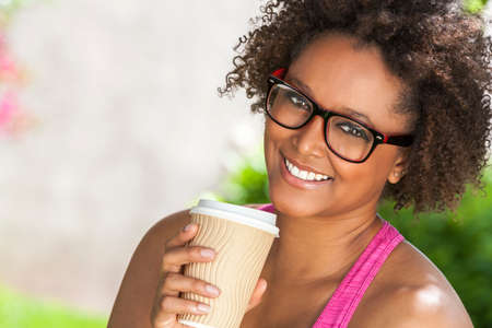 glasses eye: Beautiful young mixed race black African American woman smiling with perfect teeth, wearing glasses and drinking a takeaway cup of coffee outside