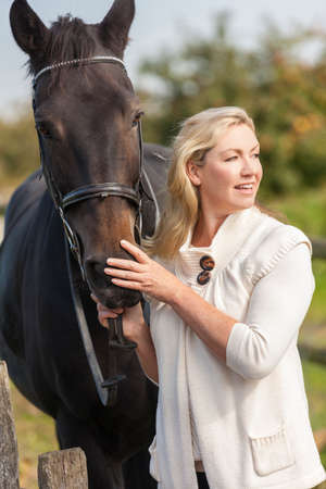 stroking: Beautiful happy middle aged woman smiling and stroking her horse outside in sunny field