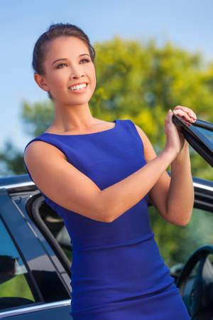 Beautiful happy successful Asian Eurasian young business woman, girl or businesswoman smiling and lgetting out if her car photo