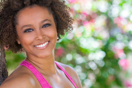woman white shirt: Beautiful young mixed race black African American woman with perfect teeth smiling and relaxing outside in summer sunshine