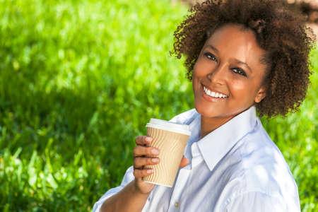 femme brune sexy: Belle jeune métis noir femme afro-américaine en souriant et en buvant une tasse à emporter du café à l'extérieur Banque d'images
