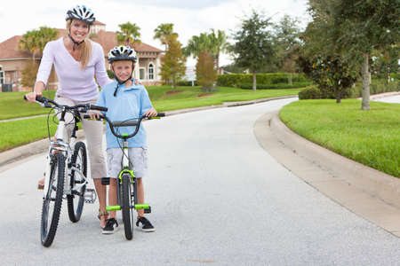 A young family of woman and boy child, mother and son, cycling together. photo