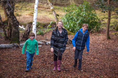 family outside: Woman and male children, mother and two sons family walking in trees of woods or forest Stock Photo