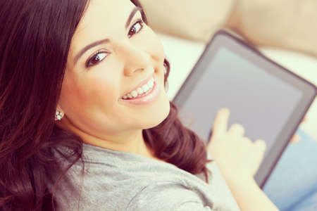 portrait of a beautiful happy young Latina Hispanic woman smiling and using a tablet computer  at home on her sofa photo