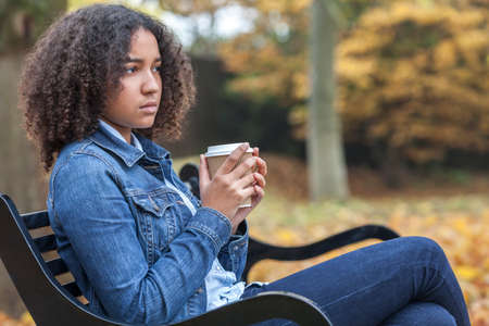 mixed race woman: Beautiful mixed race African American girl teenager female young woman drinking takeaway coffee outside sitting on a park bench in autumn or fall looking sad depressed or thoughtful