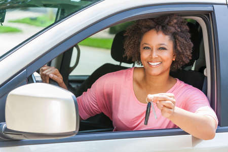 Beautiful young mixed race black African American woman driving a car and holding the key