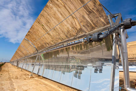 A row of parabolic trough solar mirror panels harnessing the suns rays to provide renewable alternative green energy