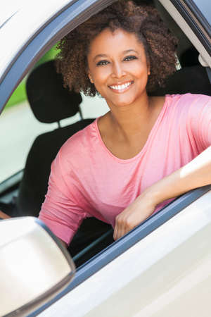 drive car: Beautiful young happy smiling mixed race black African American woman driving a car