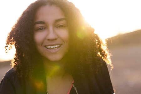 perfect teeth: Beautiful happy mixed race African American girl teenager female young woman with perfect teeth smiling in golden light with sun flare at sunset or sunrise Stock Photo