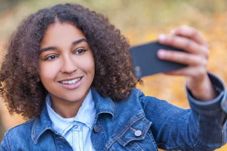 perfect teeth: Beautiful happy mixed race African American young woman girl teenager female child smiling with perfect teeth taking selfie photograph in fall or autumn