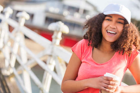 perfect teeth: Beautiful happy mixed race African American girl teenager female young woman with perfect teeth smiling drinking takeaway coffee outside wearing white baseball cap and pink t-shirt