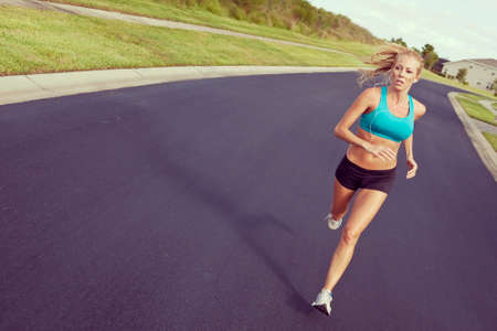 portable mp3 player: Instagram style photo of a beautiful fit and healthy blond woman road running while listening to music on her portable mp3 player Stock Photo