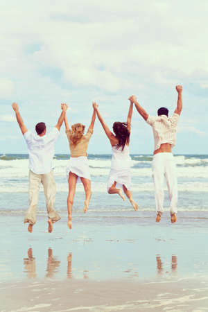Instagram style photograph of four young people, two couples, holding hands, having fun and jumping in happy celebration on a beach photo
