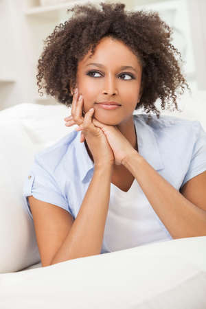 laying down: A beautiful mixed race African American girl or young woman laying down on sofa at home looking thoughtful and relaxed