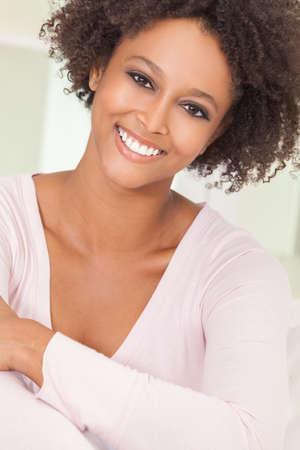 ojos marrones: Una raza mixta hermosa chica afroamericana o una mujer joven que parece feliz y sonriendo con dientes perfectos Foto de archivo