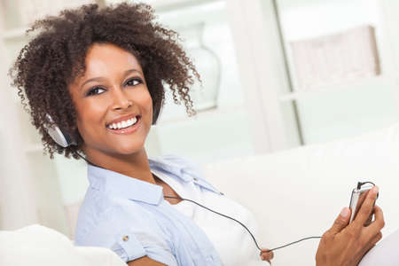 mp3 player: A beautiful mixed race African American girl or young woman relaxing at home listening to music on mp3 player and headphones Stock Photo