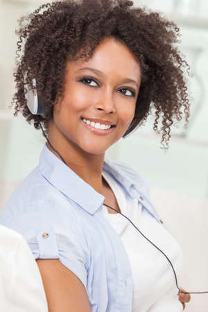 mp3 player: A beautiful mixed race African American girl or young woman listening to music on mp3 player and headphones