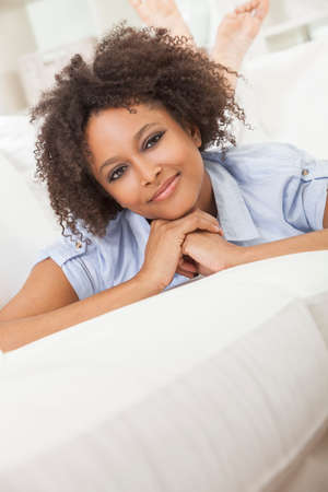 laying down: A beautiful mixed race African American girl or young woman laying down on sofa at home looking happy and relaxed