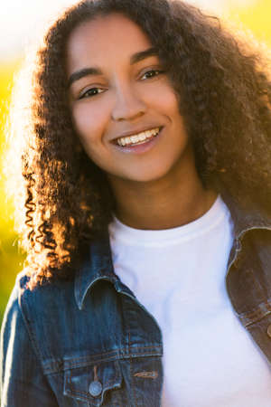 perfect teeth: Outdoor portrait of beautiful happy mixed race African American girl teenager female young woman smiling laughing with perfect teeth in golden evening sunshine