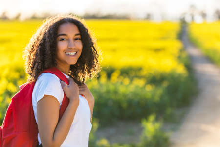 adult rape: Outdoor portrait in golden evening sunshine of beautiful happy mixed race African American girl teenager female young woman smiling laughing with perfect teeth hiking with red recksack in yellow field