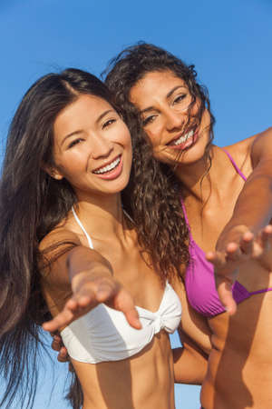 bikini couple: Two beautiful young women in bikinis having fun laughing and dancing partying together on a sunny beach with blue sky Stock Photo
