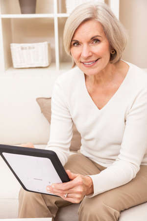 Senior woman using a tablet computer at home photo