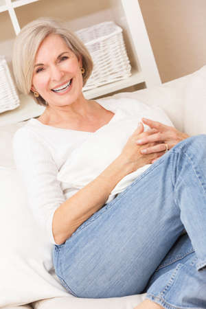 Portrait of an attractive elegant senior woman wearing jeans and relaxing at home on her sofa photo