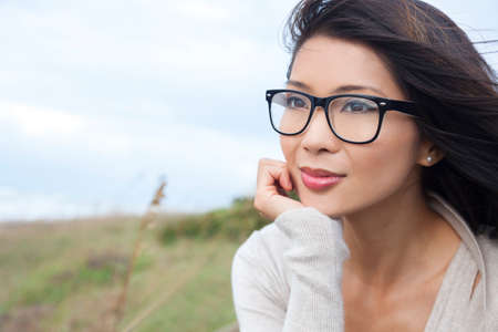 Portrait of a beautiful thoughtful chinese asian girl or young woman outside wearing glasses Stock Photo