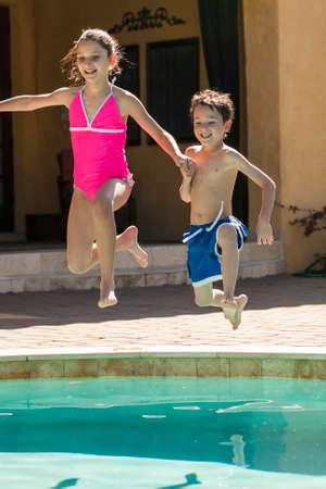 Two children boy and girl laughing having fun jumping into swimming pool photo