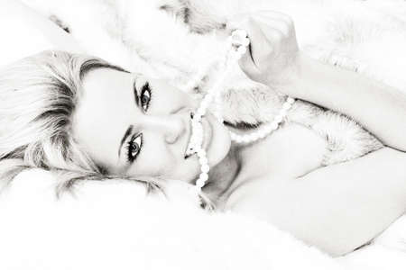 fur: Black and white photograph beautiful young blond woman or girl in bed wrapped in (fake) fur and biting a pearl necklace