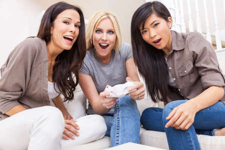 Three beautiful interracial young women friends at home having fun playing video console games together and laughing photo
