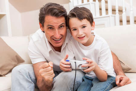 Man and male boy child, father and son having fun playing video computer console game together using handset controller on sofa at home photo