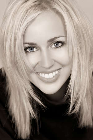 blond haired: Black and white studio shot of a beautiful happy blond haired blue eyed woman with perfect teeth and smile Stock Photo