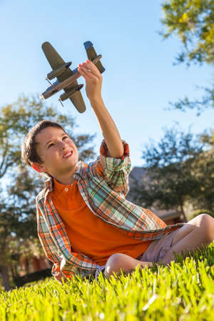 A young boy sitting on grass outside playing with a toy model airplane photo