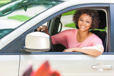 mujeres africanas: Hermosa joven de raza mixta negro mujer afroamericana que conduce un coche