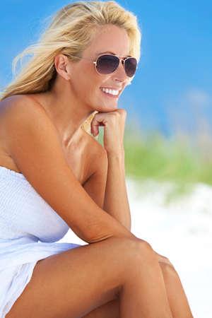 mujer alegre: Una joven bella mujer rubia sonriente en gafas de sol de aviador y una sundress blanca, sentado en una playa tropical desierta Foto de archivo